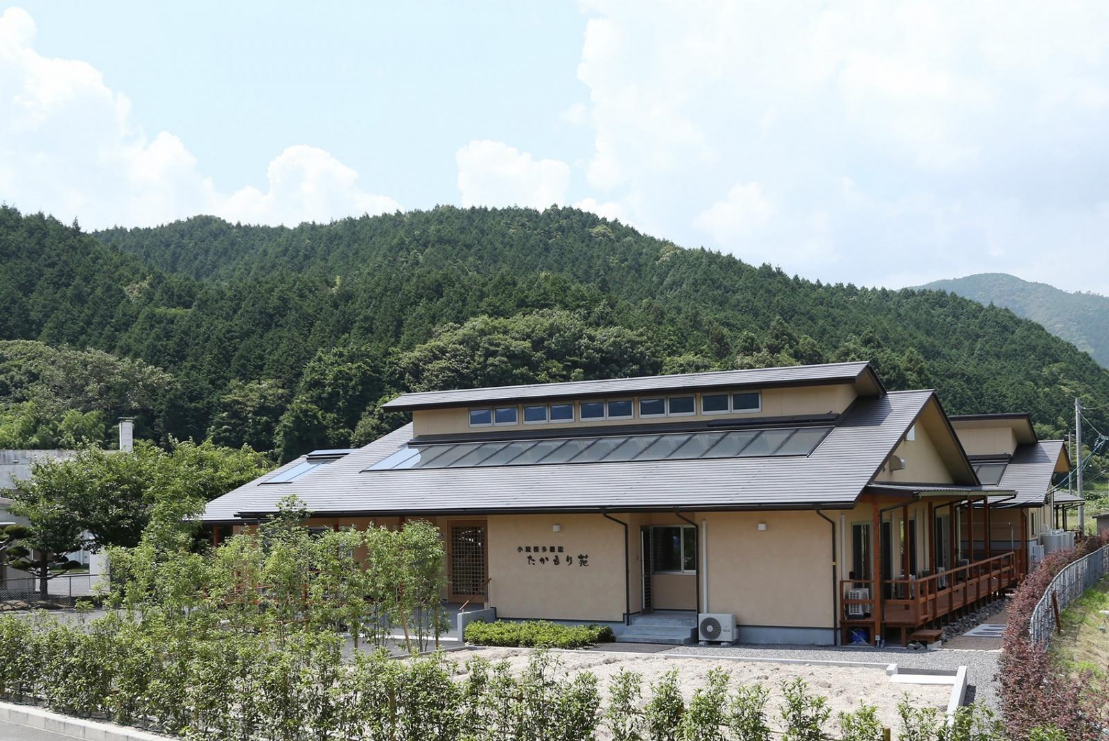 たかもり苑外観。屋根に見えるのがOMソーラーの太陽熱の集熱面。冬季は屋根で集めた熱を床下に送り込むことで建物全体がじんわりとあたためられる。屋根の上の小屋部分にFIX窓を設けることで自然光で室内を明るく保つことができる工夫も。