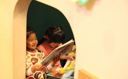 読書コーナーで仲良く本を読む。子どもがこもれる空間も設けられている。