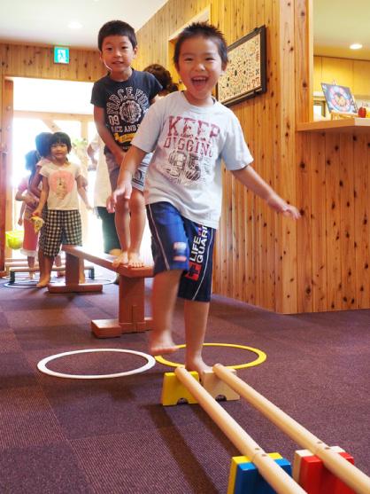 運動器具のあるエントランスホールを通ってランチホールに向かう子どもたち。