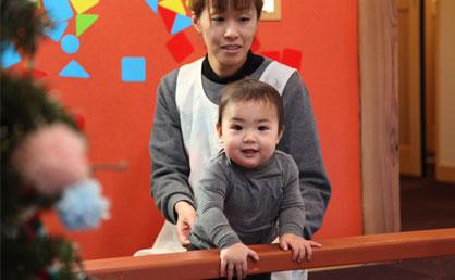 乳児は先生と一緒に運動器具に親しむ。